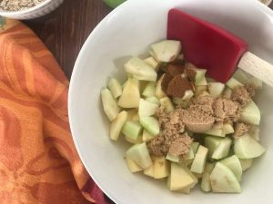 Diced apples in a white bowl with cinnamon and brown sugar