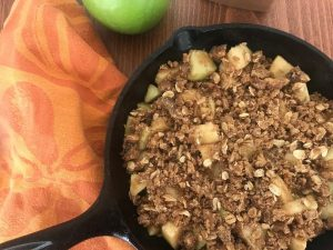 Crumb topping on diced apples in a cast iron pan