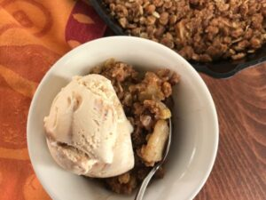 scoop of ice cream on apple crisp in a white bowl