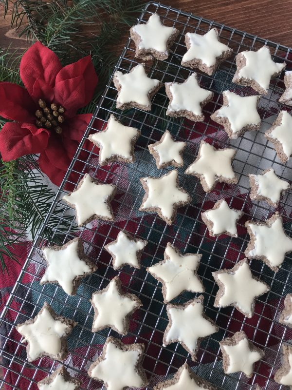 Zimtsterne on a wire cooling rack with a poinsettia next to cooling rack