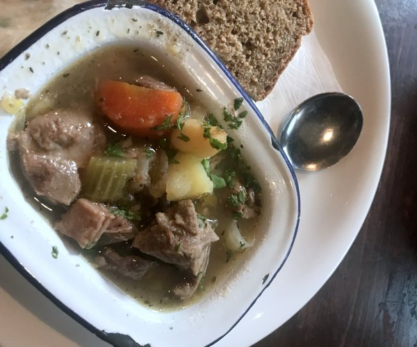 Irish stew in a blue rimmed rectangle bowl, on a white plate with a spoon and slice of brown bread