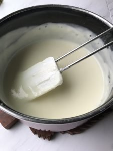 sour cream, butter, salt, and  sugar in a sauce pan with a white and metal spatula