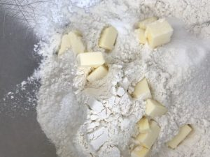 flour, sugar, baking soda,and salt with cubed butter. in a metal bowl