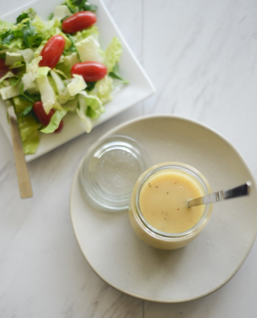 Finished vinaigrette in a glass jar. Spoon in the jar. Jar on a plate