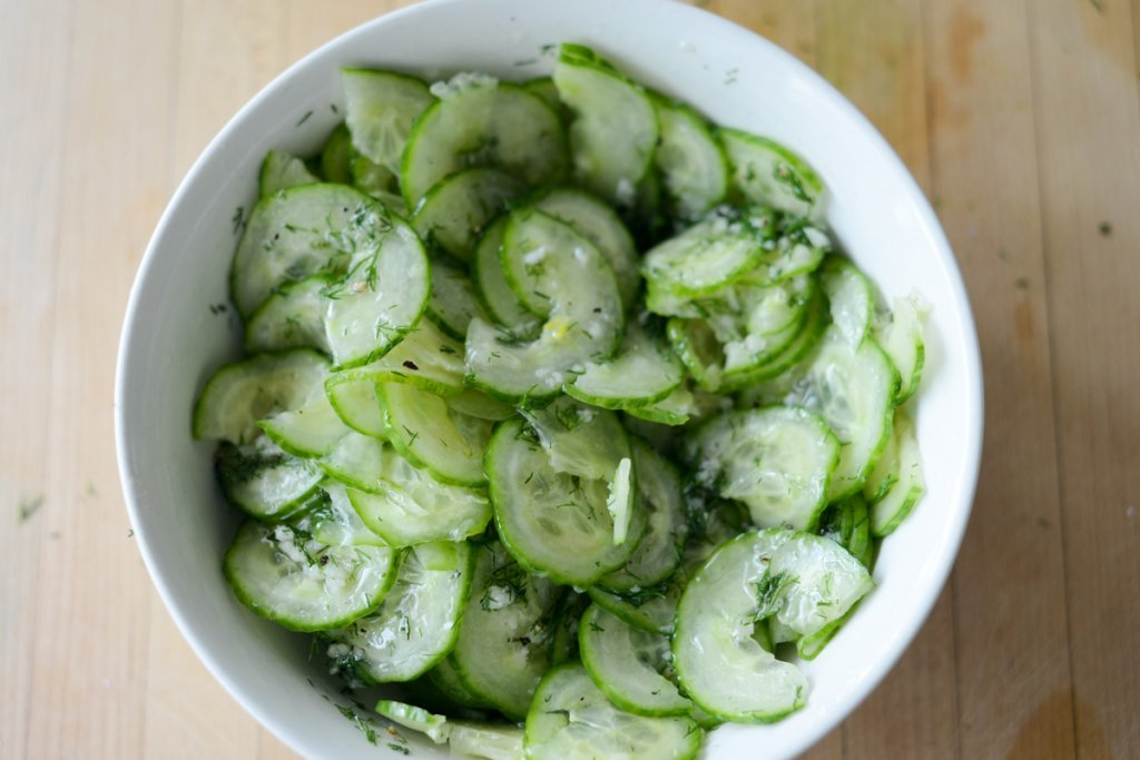 Top view of cucumber salad in white bowl tossed with vinaigrette