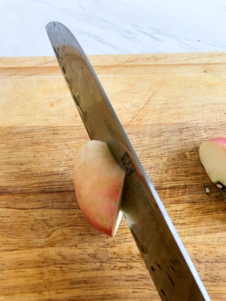 Removing the apple core with a chefs knife on a cutting board