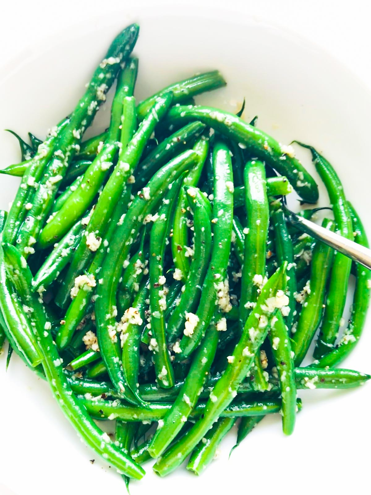 Top view green beans in a white serving bowl