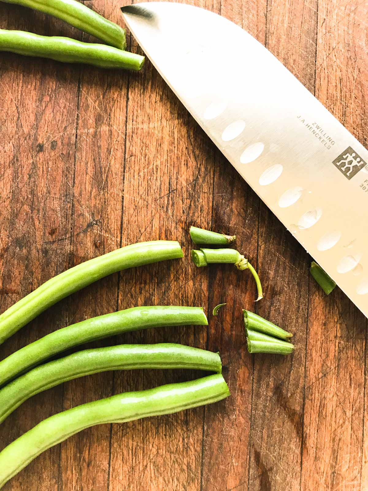 Trimmed green beans with a knife on a cutting board
