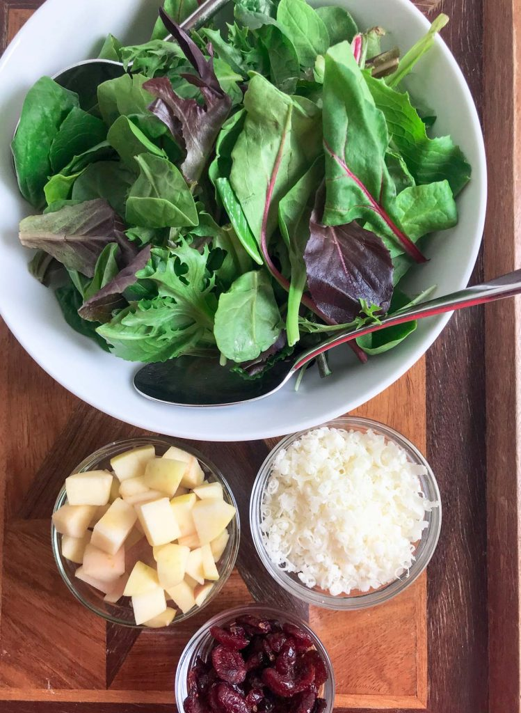 Mixed salad greens in a white bowl with a spoon.  Diced apple in a small glass bowl next to white salad bowl.  Grated Parmesan cheese in a glass bowl next to white bowl.  On wooden board.