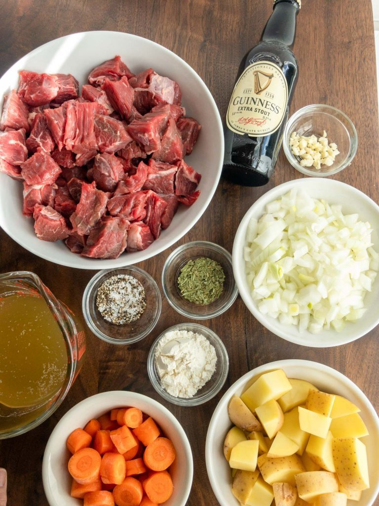 ingredients for stew, beef , Guinness stout beer, onions, garlic, tarragon, flour, carrots, potatoes and stock