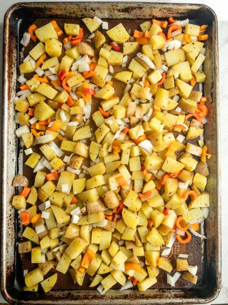 diced potatoes and onions and peppers on a sheet pan