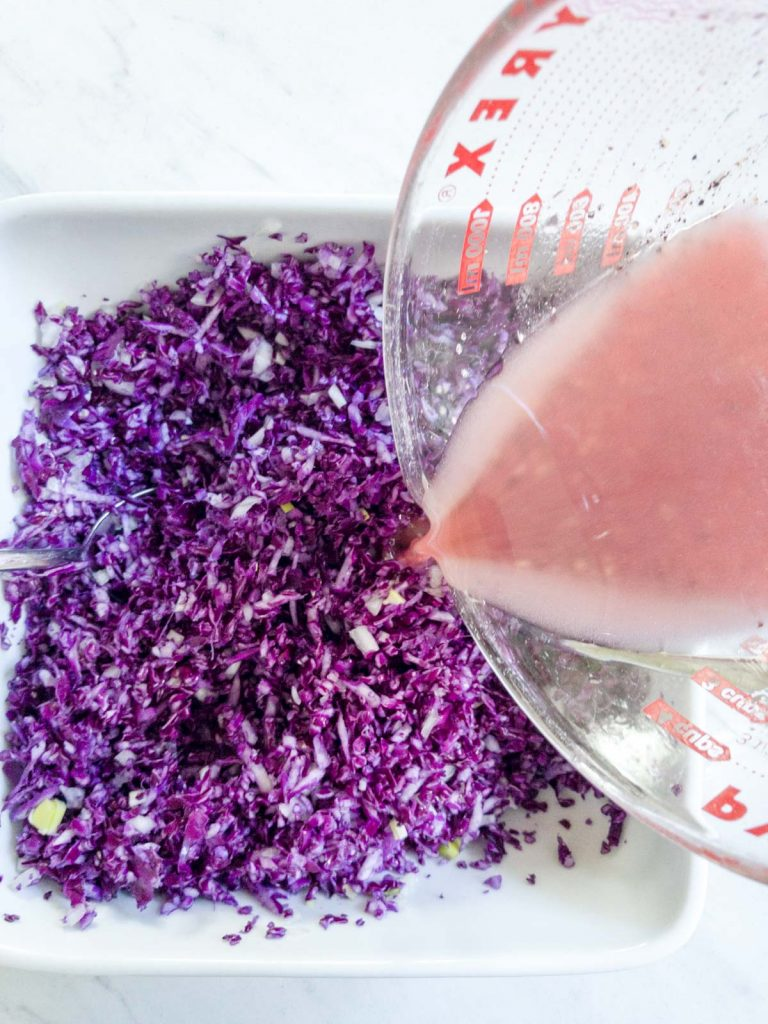 Pouring vinaigrette on the red cabbage