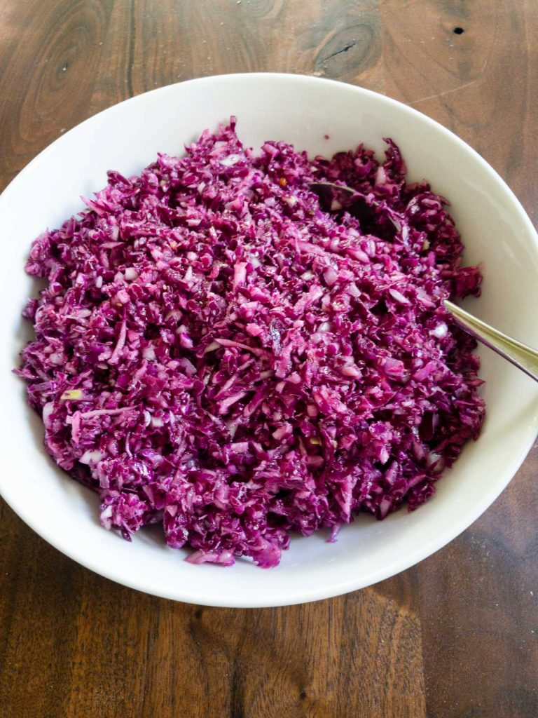 Finished red cabbage salad in a white bowl top view