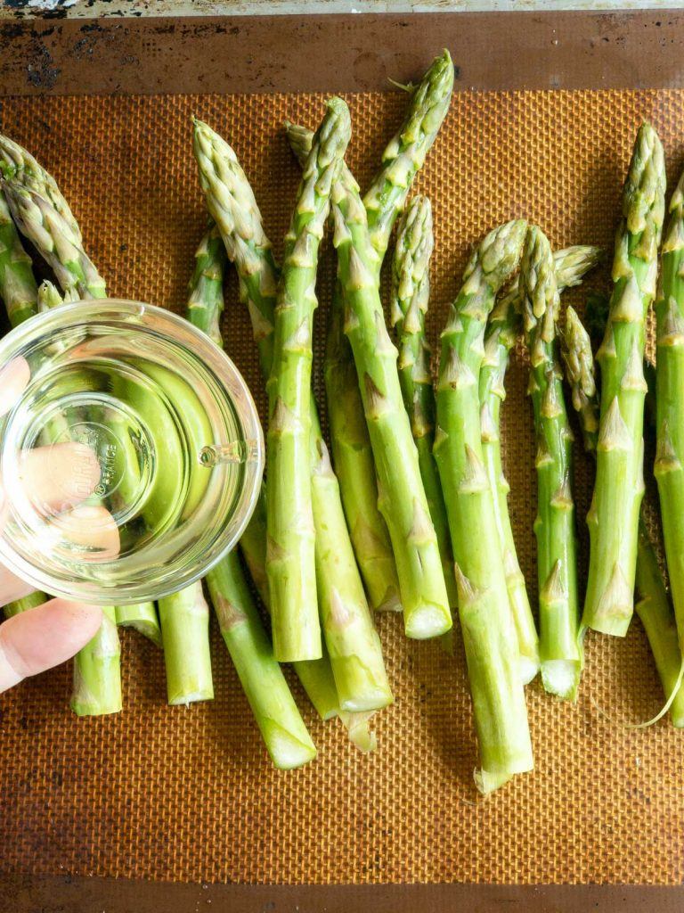 Adding olive oil on the asparagus that are on a sheet pan