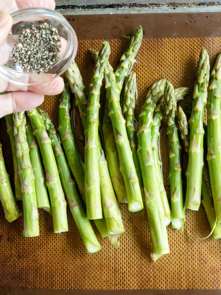 Add pepper to asparagus on a sheet pan