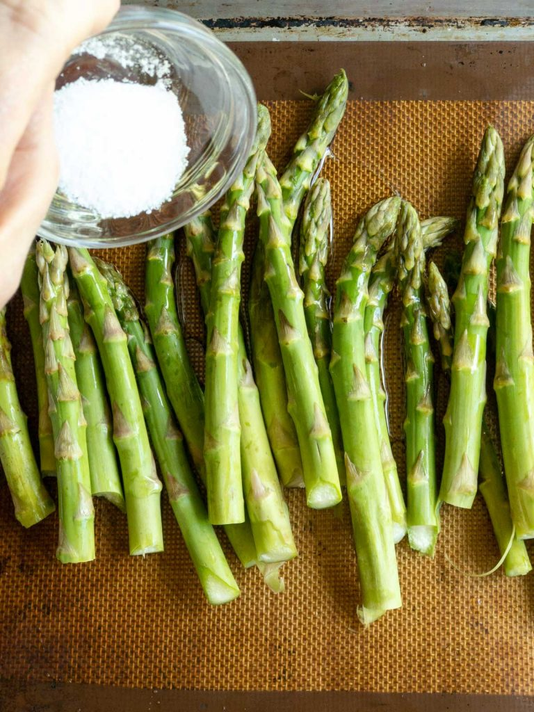 Sprinkle salt on the asparagus on sheet pan