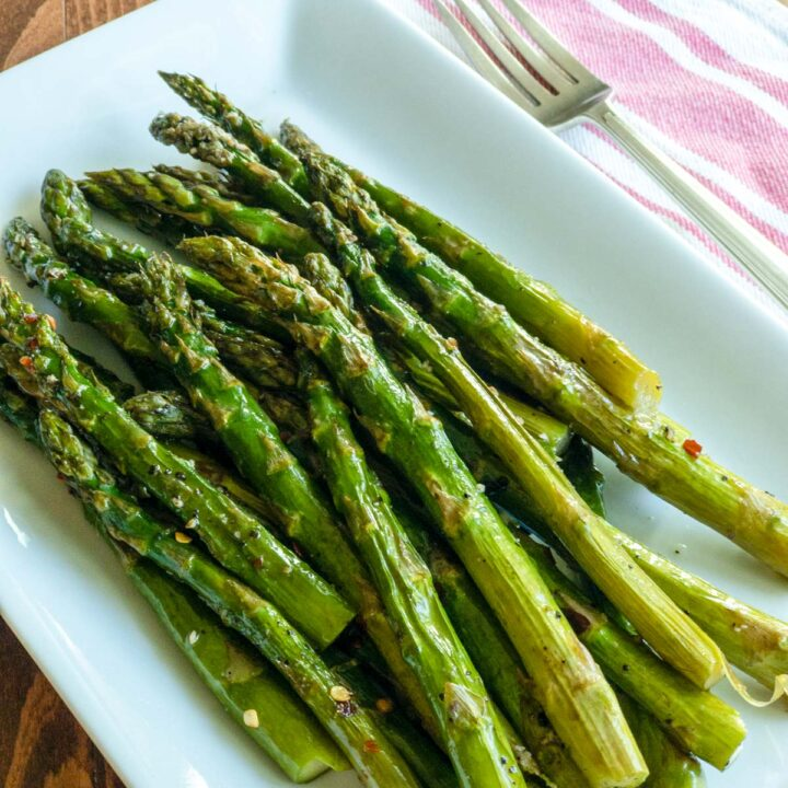 Asparagus on white rectangle dish with fork next to it