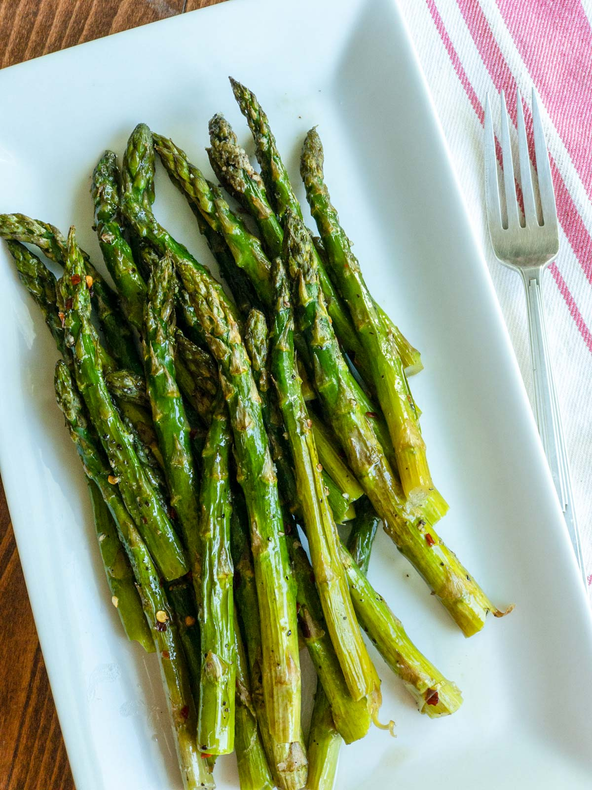 Roasted asparagus on white rectangle dish with a fork next to it