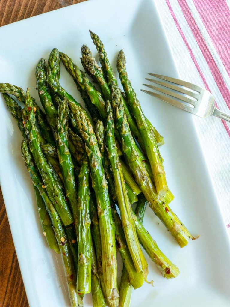 Top view of asparagus on a white plate