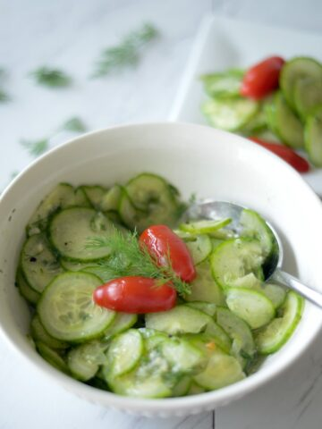 Top view of cucumber salad in white bowl