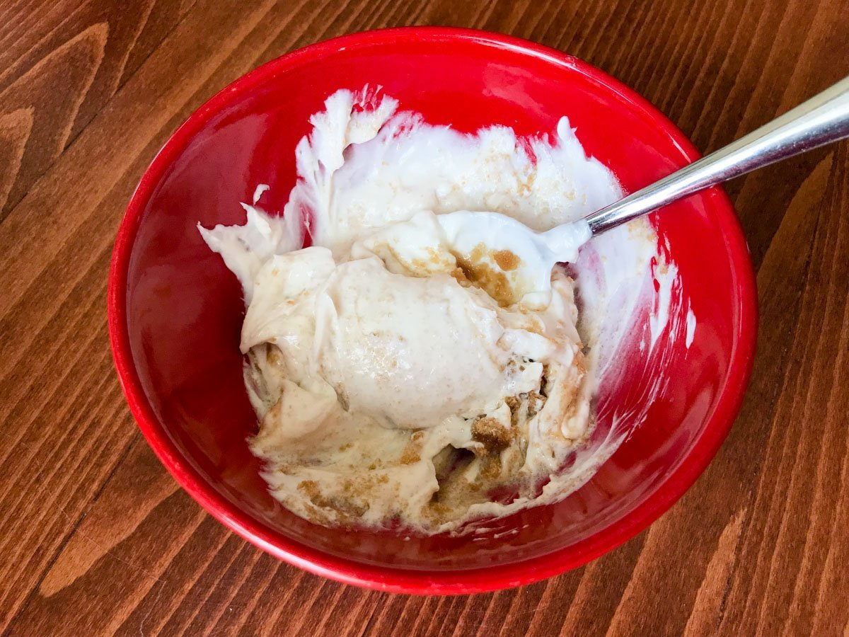 Brown sugar, vanilla and yogurt in a red bowl partially combined