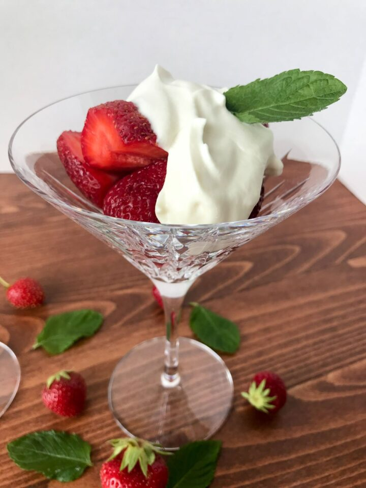 Side view of strawberry romanoff in a martini glass. Strawberries topped with cream mixture and garnished with mint leave.