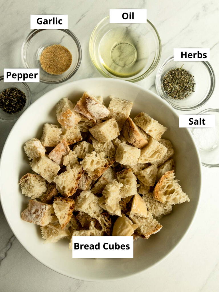 Bread cubes in a bowl. The following in clear bowls: salt, herbs, oil, garlic powder and pepper