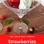 Strawberries topped with cream in a martini glass on a wood table