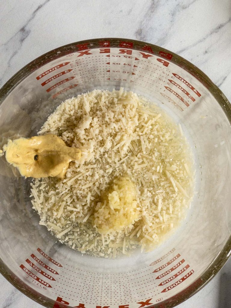 Mustard, pressed garlic and Parmesan cheese in a Pyrex measuring cup