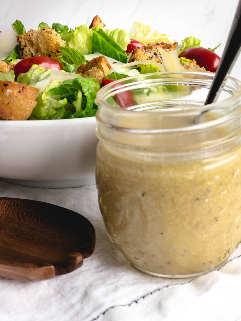 Caesar salad dressing in a glass jar with a white bowl of salad