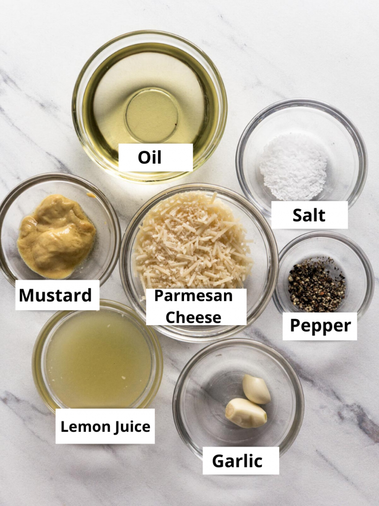 Labeled ingredients for a Caesar salad dressing in individual glass bowls on a white surface, oil, salt, pepper, garlic cloves, mustard, lemon juice, Parmesan cheese