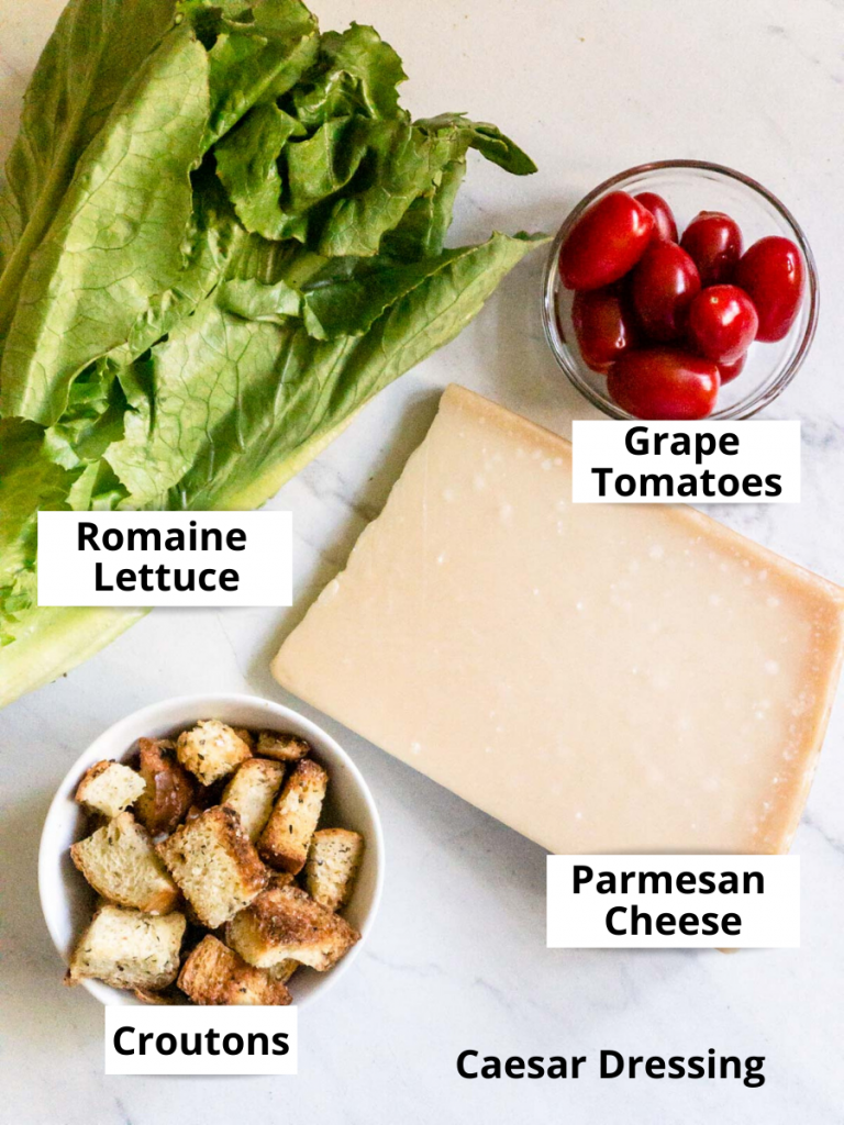 labeled ingredients on a white stone, Romaine lettuce, grape tomatoes, chunk of Parmesan cheese and croutons