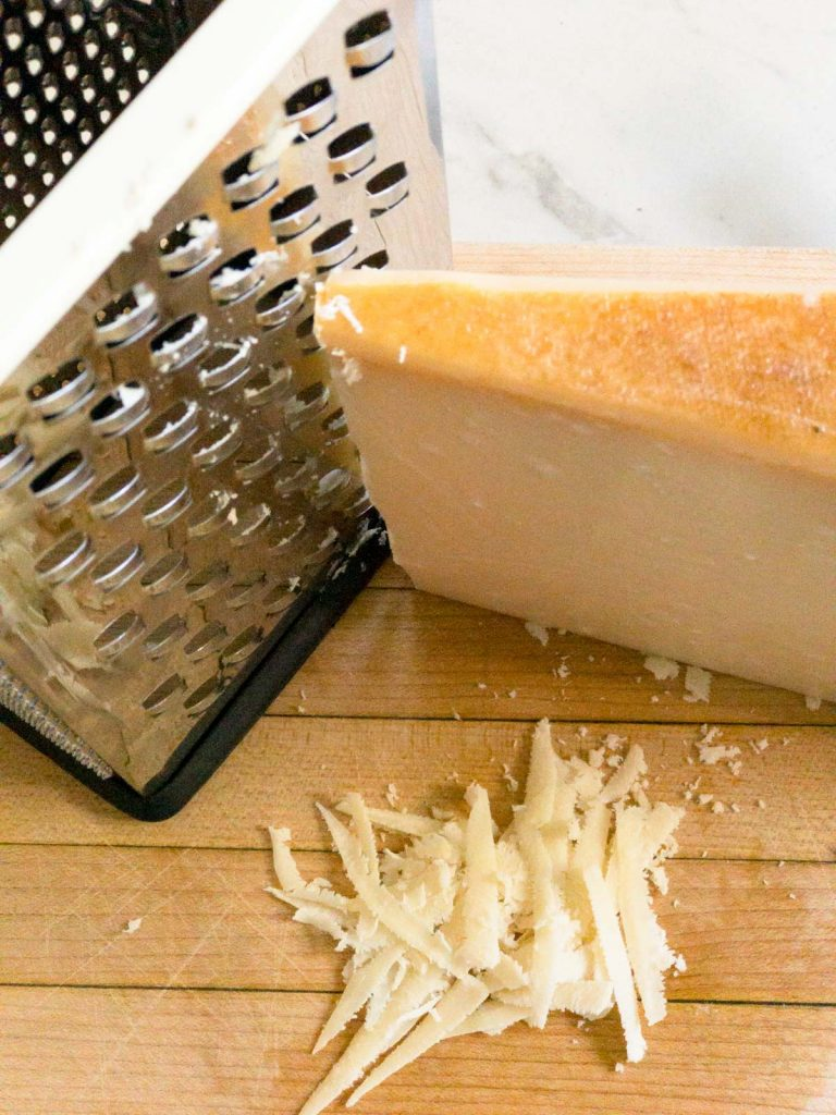 box grater with Parmesan cheese and grated cheese next to it on a wood cutting board