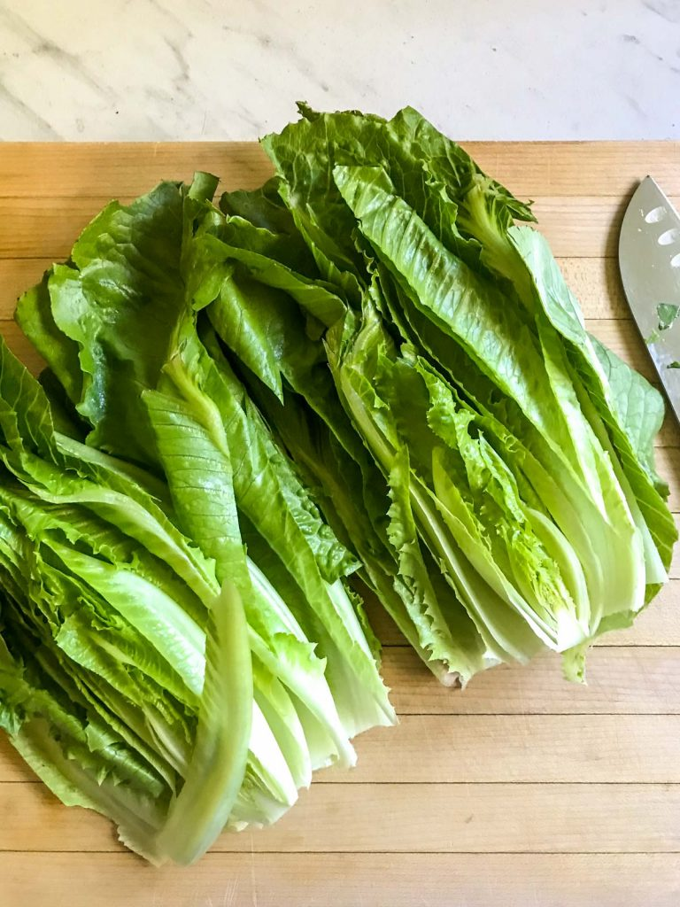 sliced romaine lettuce on a wood cutting board with a chefs knife next to it