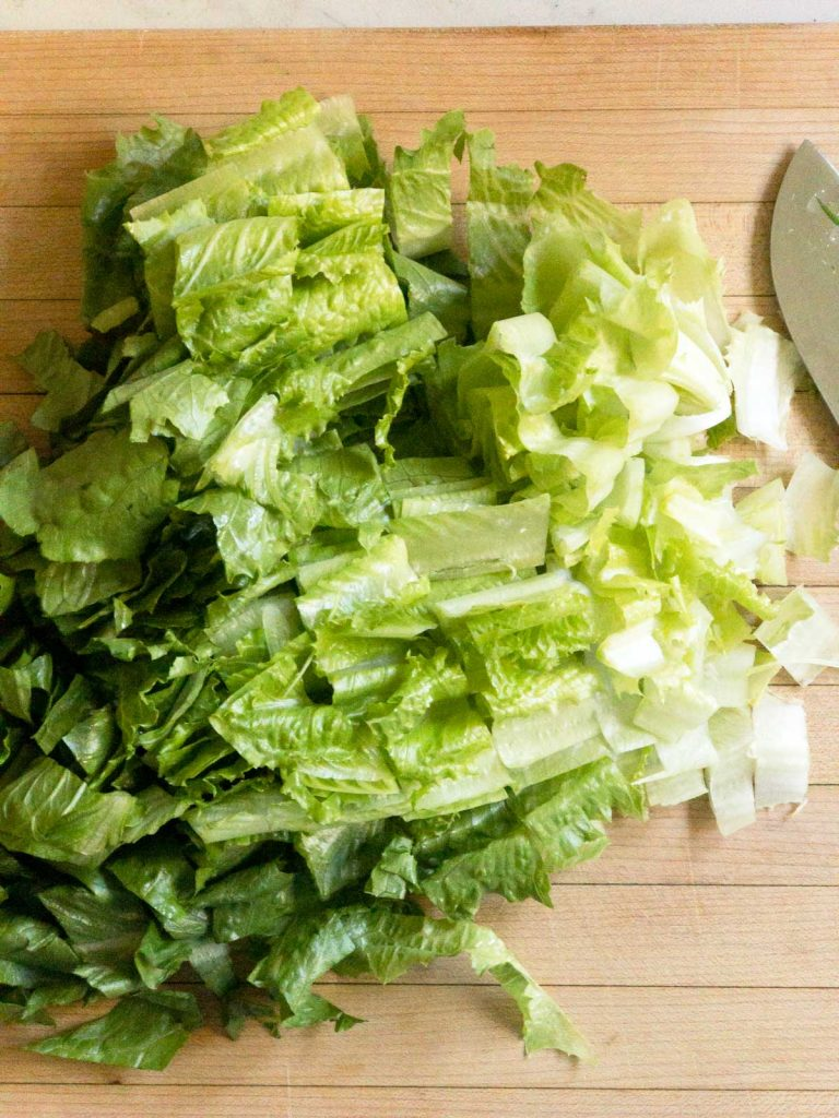 chopped romaine lettuce on a wood cutting board