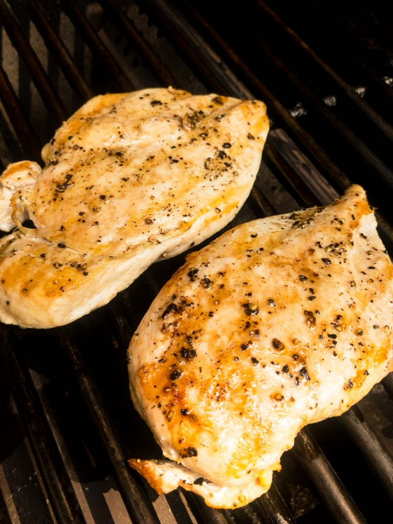 Cooked chicken breasts on a grill grate