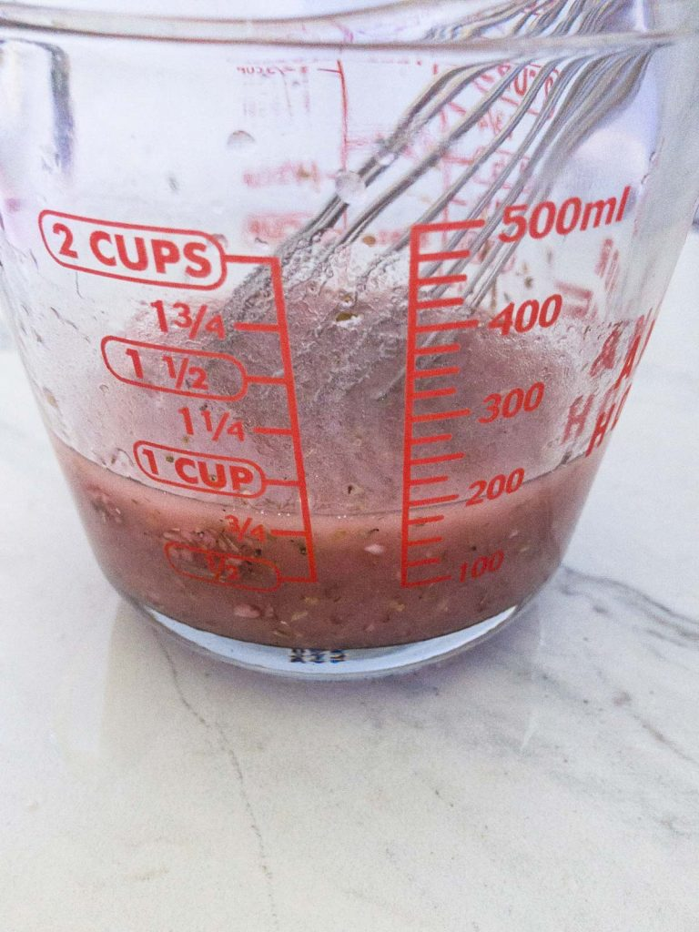 Greek salad dressing in a measuring cup