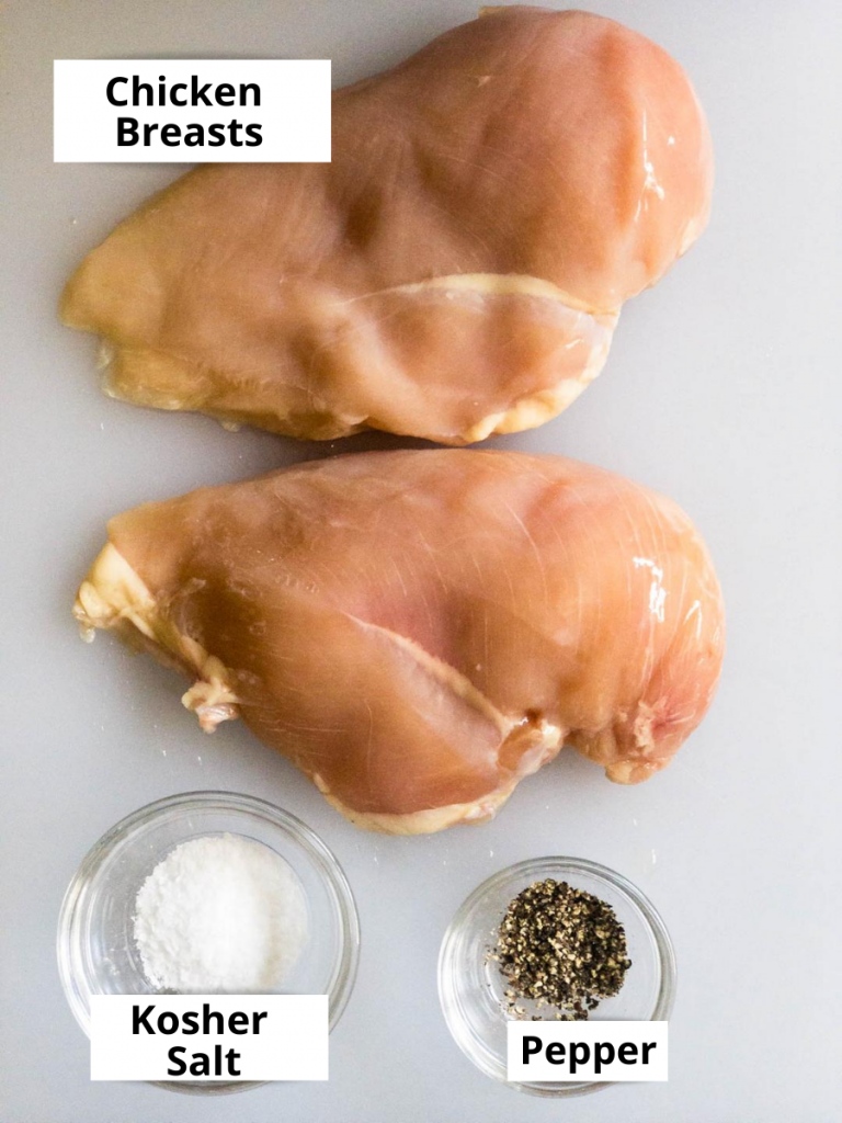 Raw chicken breasts, salt and pepper on a white cutting board