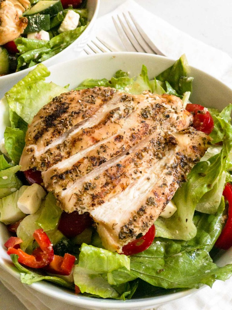 Sliced grilled chicken on a Greek salad in a white bowl.