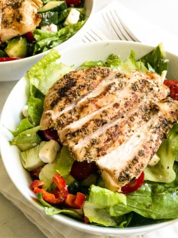 Grilled chicken on Greek salad in white bowl