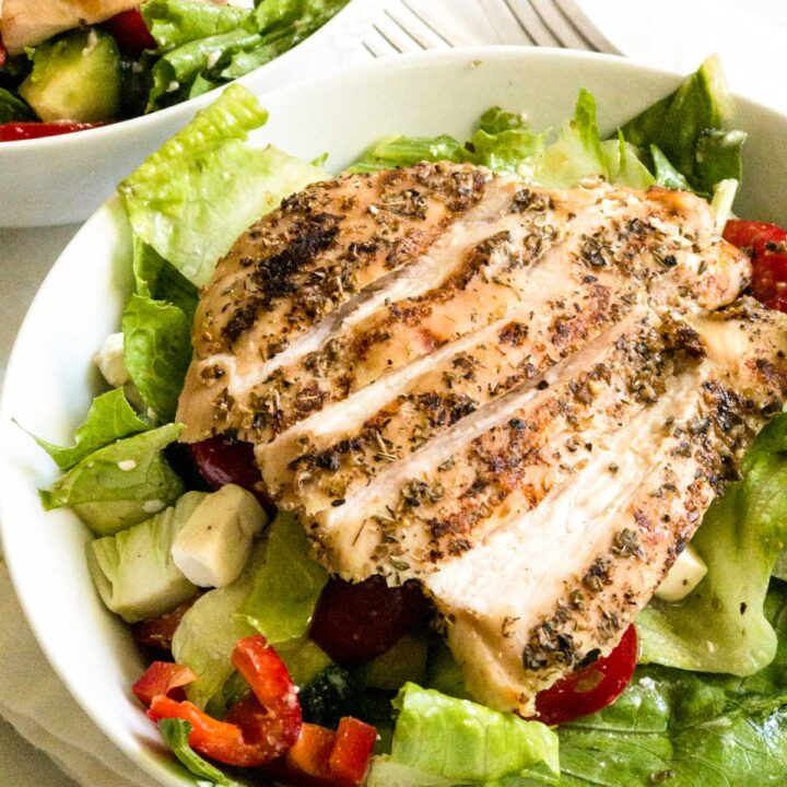 Grilled chicken on Greek salad in white bowl