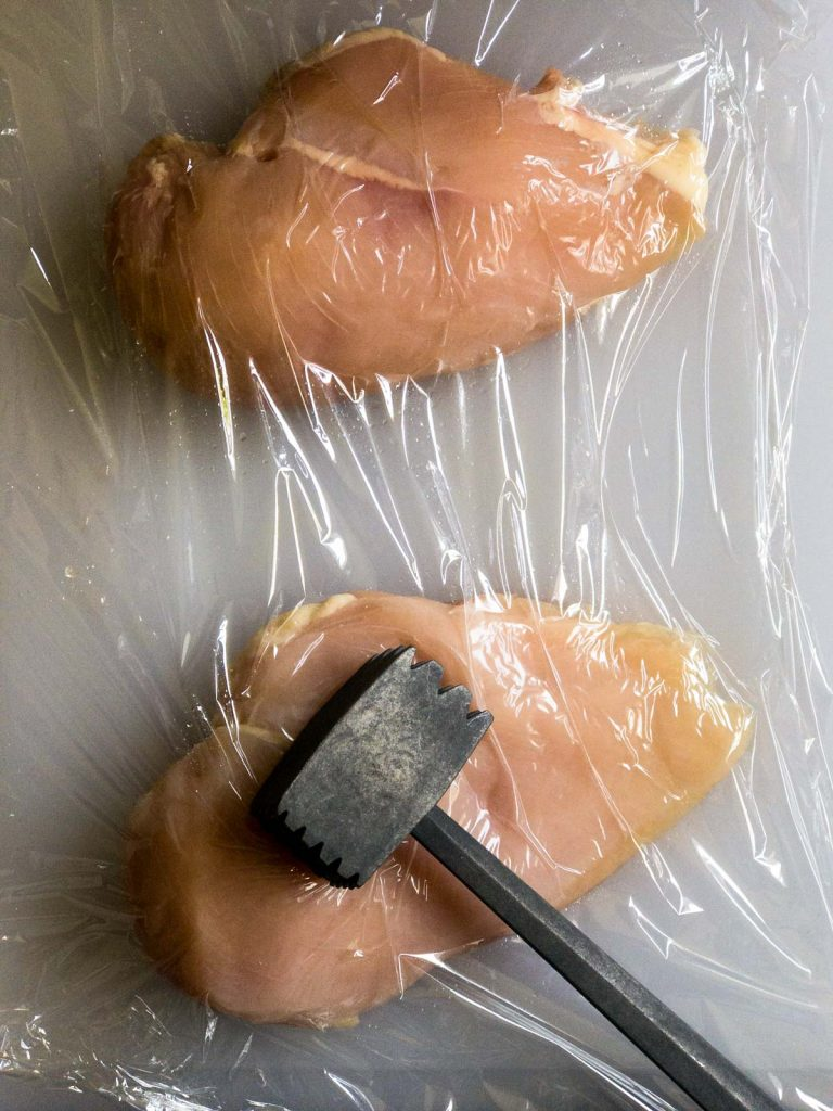 Raw chicken breasts on a white cutting board, sheet of plastic wrap on top of chicken, meal mallet on chicken breast
