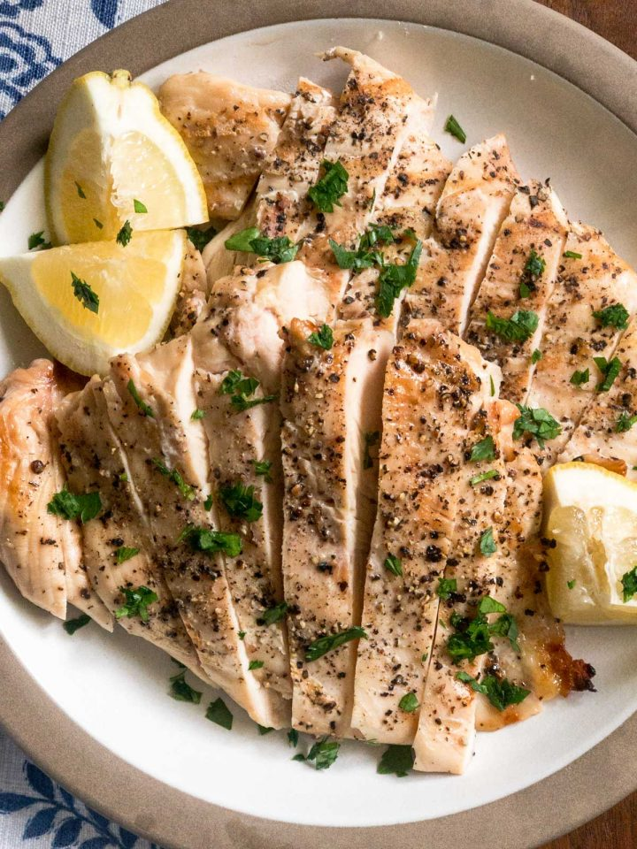 Sliced grilled chicken with lemon wedges on a plate