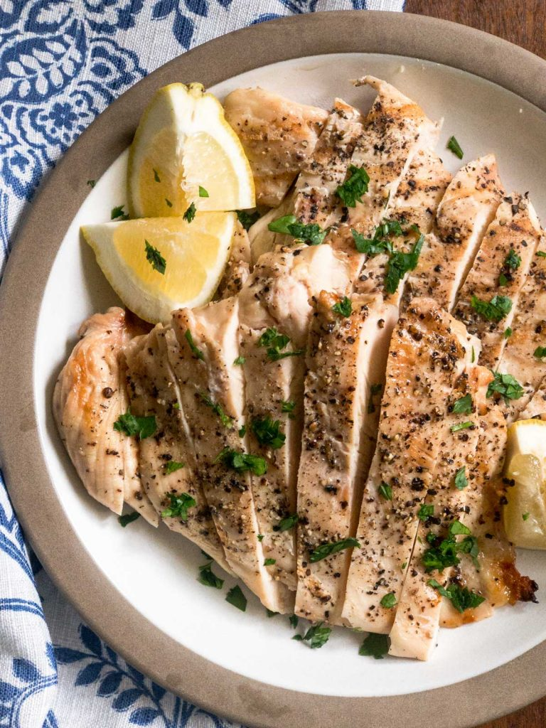 Top view of sliced grilled chicken breasts on a tan plate
