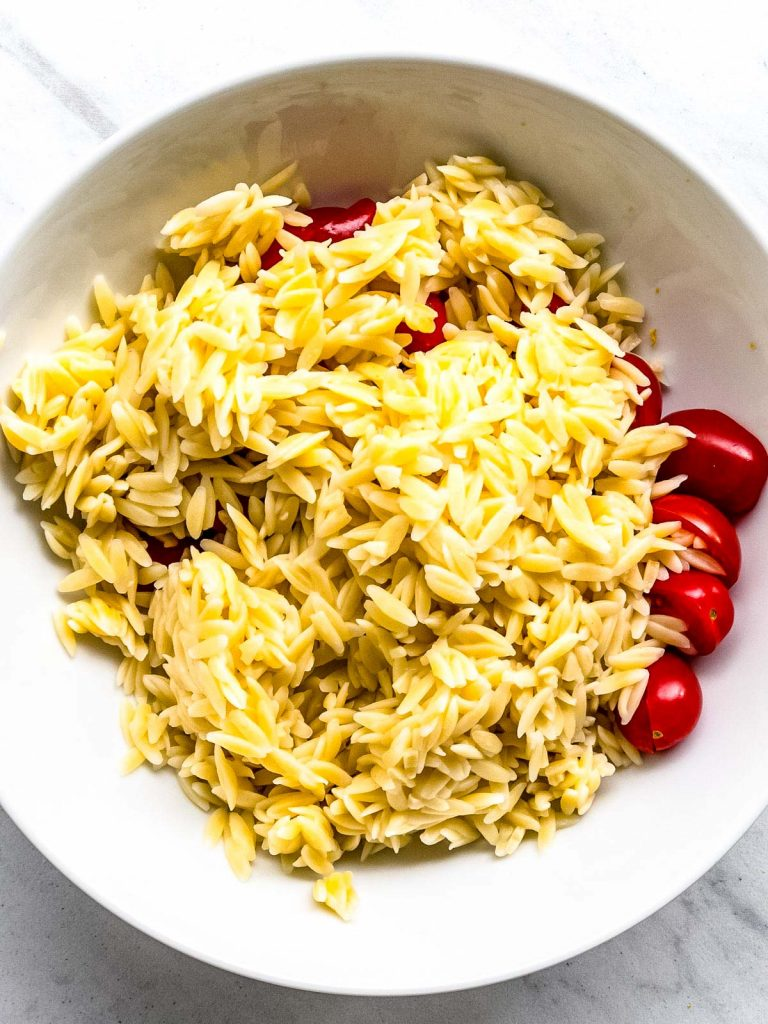 Cooked orzo pasta on top of tomatoes