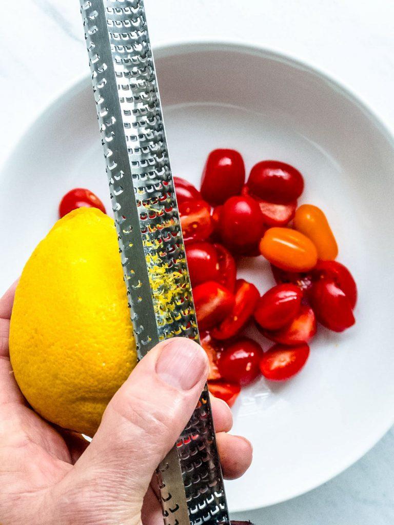 Zesting lemon on tomatoes