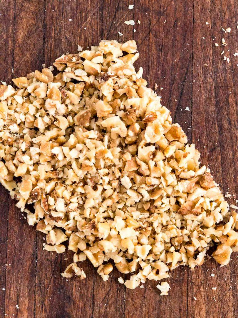 Rough chopped walnuts on a cutting board