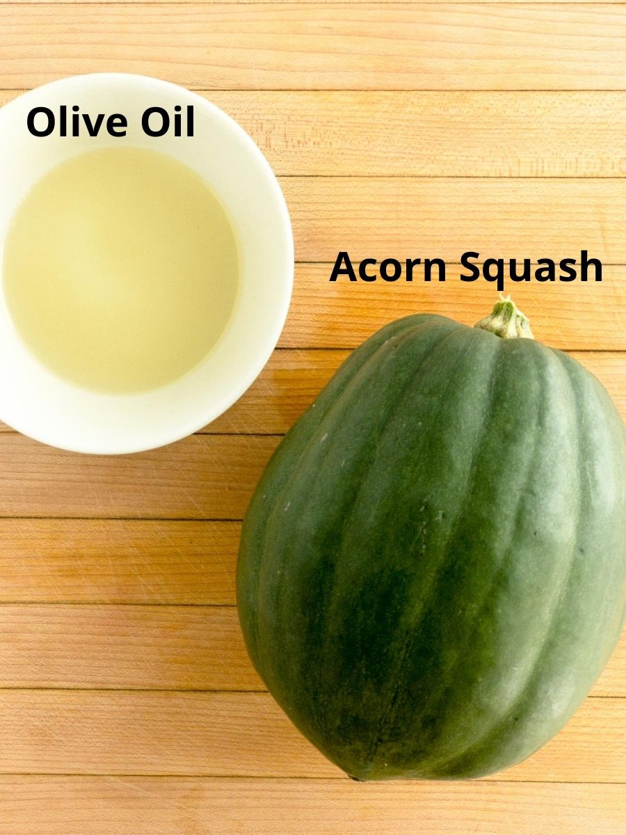 Acorn squash on a cutting board and olive oil in a bowl