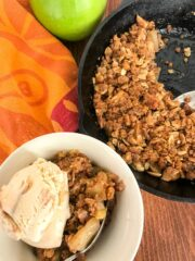 Skillet apple crisp in a cast iron pan and in a white servine bowl with ice cream on top