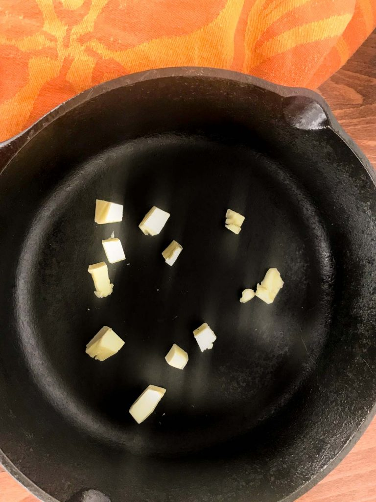 Pieces of butter scattered in a cast iron pan